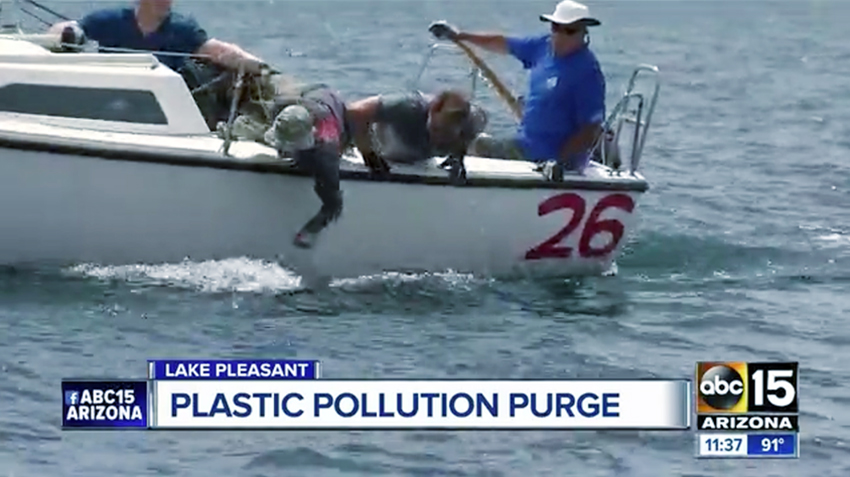 People in a sailboat reach into the water to pick up trash